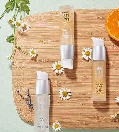 nu skin products arranged on tray with flowers and orange slice