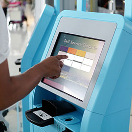 Person buying plane ticket at self-serve kiosk